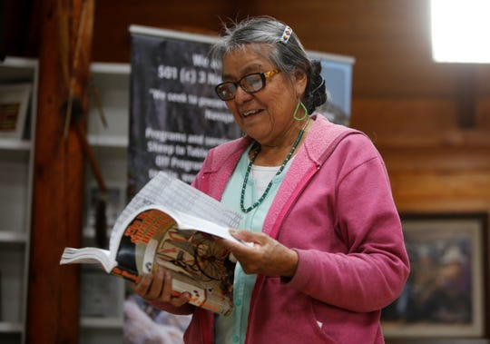 Lois Becenti, a member of Diné Bé' Iiná Inc., looks through a book about weaving on Friday at Navajo Technical University in Crownpoint.