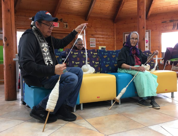 Gilbert Begay, left, and Annie A. James spin wool during the Crownpoint Spin Off sponsored by Diné Bé' Iiná Inc. on Friday at Navajo Technical University.