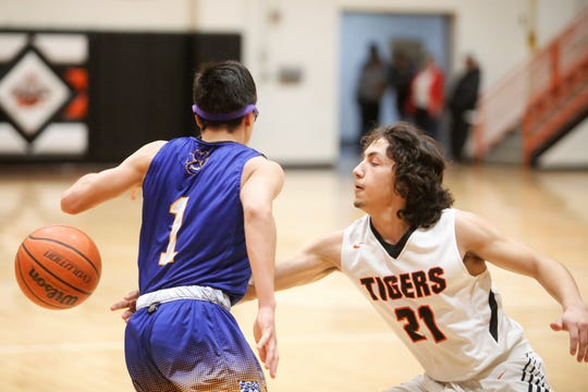 Aztec's Javier Valenzuela pokes the ball out of the hands of Bloomfield's Rogelio Gonzales during Thursday's District 1-4A game at Lillywhite Gym in Aztec. Visit daily-times.com to see the latest sports photo galleries and video highlights.