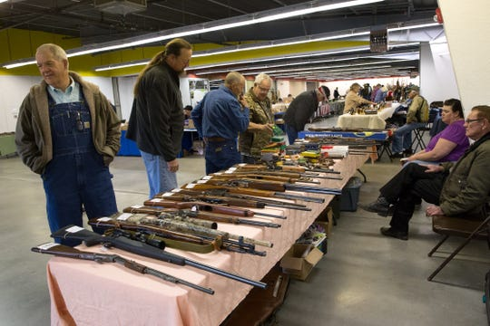 Gun enthusiasts look over items on display by vendors in this 2017 file photo during the San Juan Federation Gun and Knife Show at McGee Park in Farmington.