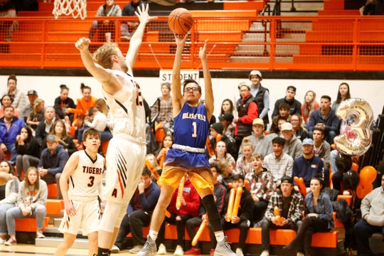 Bloomfield's Rogelio Gonzales shoots a jumper against Aztec's Dom Faverino during Thursday's District 1-4A game at Lillywhite Gym in Aztec.