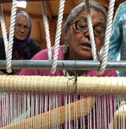 Lois Becenti sets the batter stick inside the wool warp on a weaving loom during the Crownpoint Spin Off at Navajo Technical University on Friday.
