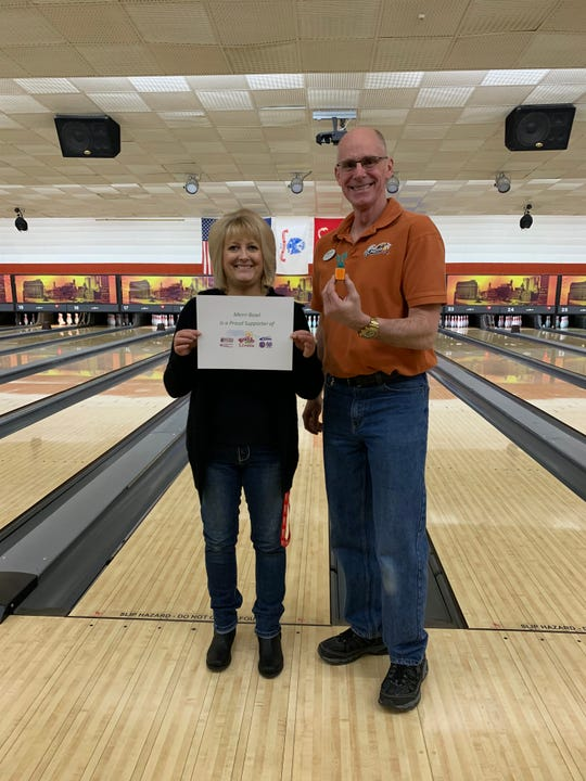 Rich Glomb, an owner of Merri-Bowl and Teri Gasser, supervisor, hold up a Carrot beacon at the bowling alley on Five Mile. Merri-Bowl is one of a dozen locations across Livonia with beacons, which earns those using the Carrot app an additional 1,000 steps.