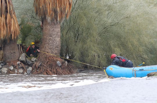 A teen, left, tries to help rescue crews after being stranded in the storm water channel that runs through Mesquite Country Club in Palm Springs during heavy rains, February 14, 2019.