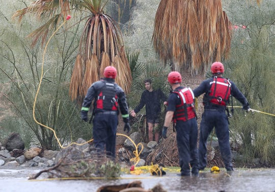 Emergency crews work to reach a teen who was stranded in the stormwater channel that runs through Mesquite Country Club in Palm Springs during heavy rains, February 14, 2019.