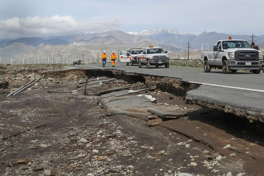 A crew from Caltrans surveys the damage where parts of Highway 111 were washed away by an overwhelming amount of rain water in Palm Springs, February 15, 2019.