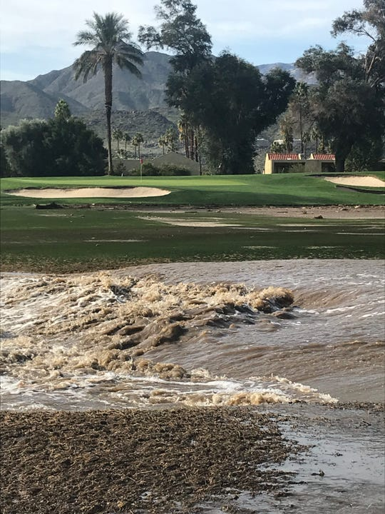 Flood waters cut across the 17th fairway of the Legend Course at Tahquitz Creek Golf Resort in Palm Springs Friday