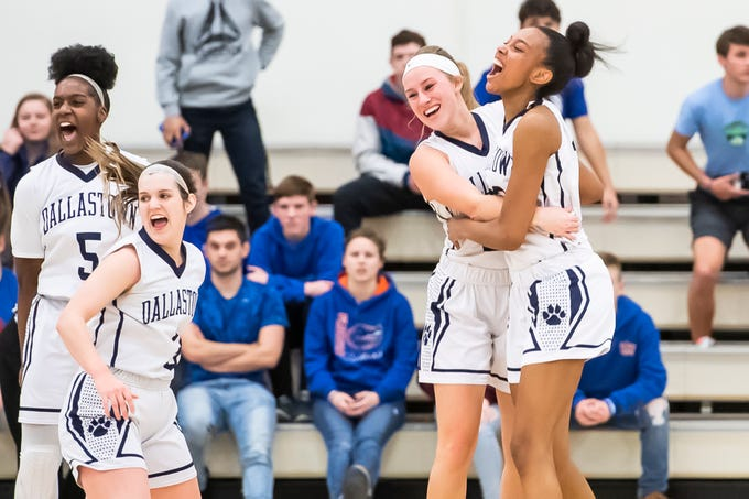 (From left) Dallastown's D'Shantae Edwards, Claire Teyral, Lily Jamison and Aniya Matthews celebrate their 36-26 YAIAA girls' championship win against Spring Grove at Charles Wolf Gym at York College Thursday, February 14, 2019.
