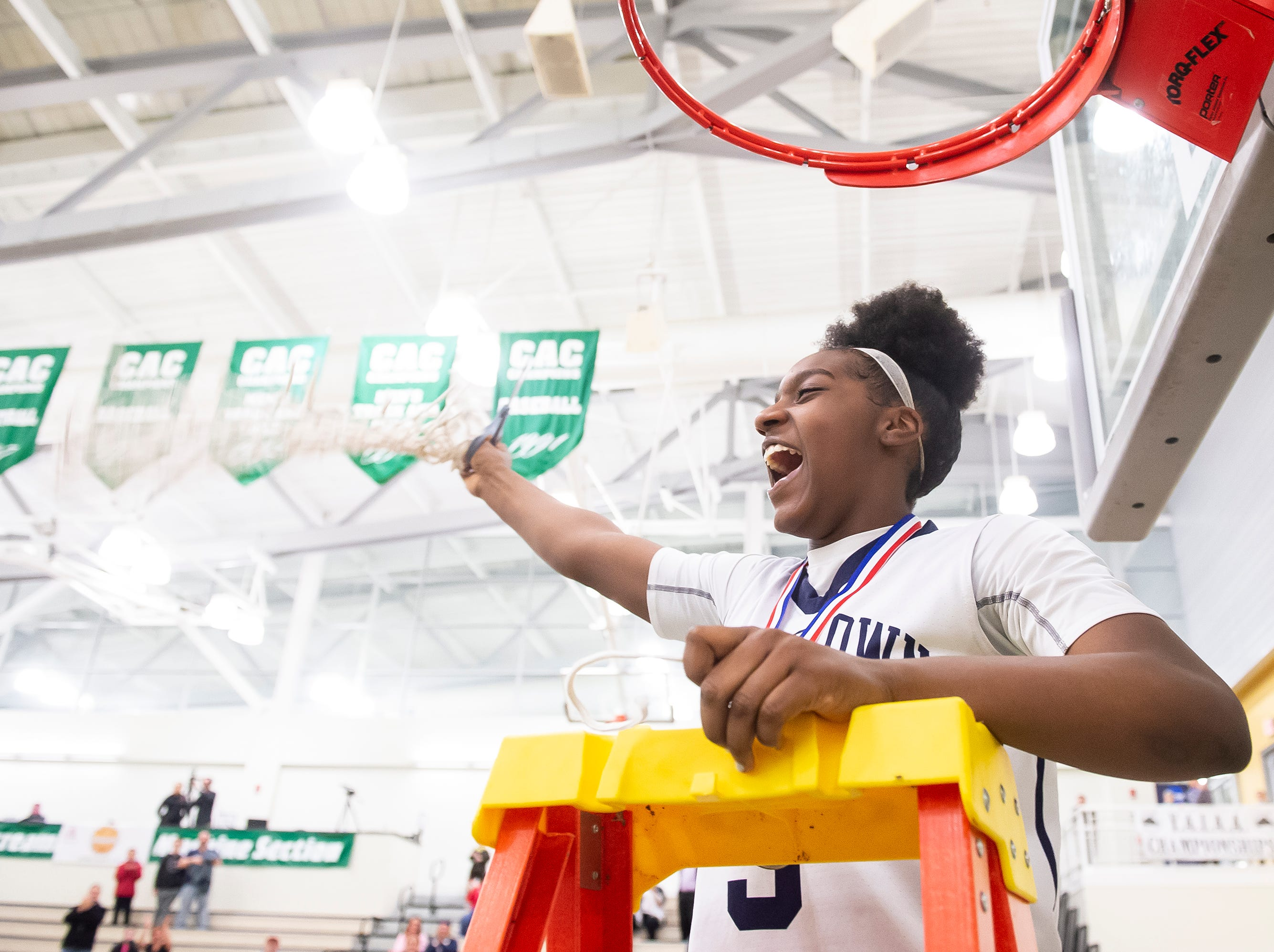 Dallastown's D'Shantae Edwards waves the net after cutting the down as the Wildcats defeated Spring Grove in the  YAIAA girls' championship game at Charles Wolf Gym at York College Thursday, February 14, 2019. The Wildcats won 36-26.