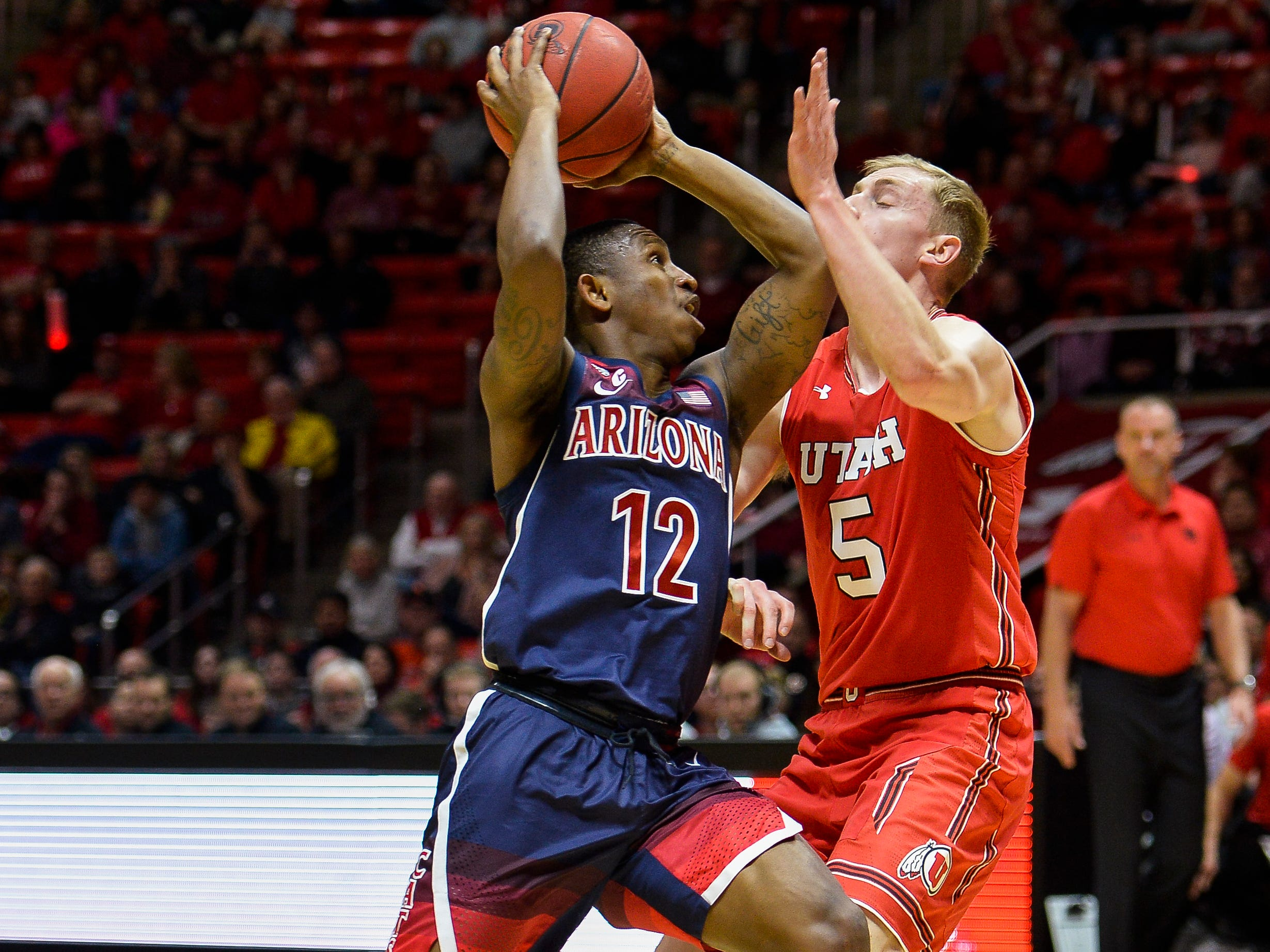 Arizona guard Justin Coleman (12) attempts to drive past Utah guard Parker Van Dyke (5) during the first half of an NCAA college basketball game Thursday, Feb. 14, 2019, in Salt Lake City.