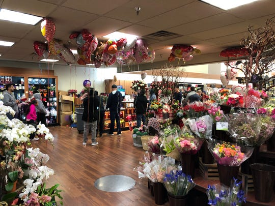 Last-minute shoppers stand in line at the Safeway flower desk.