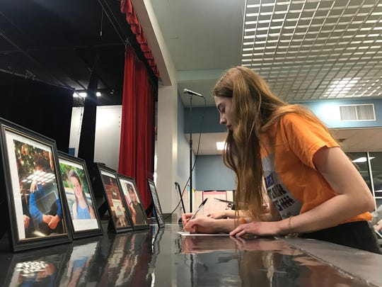 Emma Rowland, 18, writes the names of the Florida mass-shooting victims on their pictures during a vigil on Feb. 14, 2019.