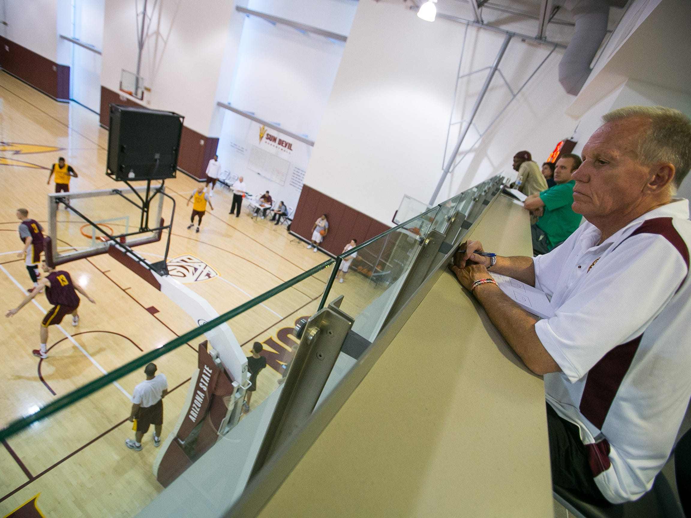 Former NBA player/coach and ESPN analyst Doug Collins takes notes during ASU men's basketball practice at the Weatherup Center in Tempe on Feb. 11, 2014. The basketball practice facility was completed in 2009.