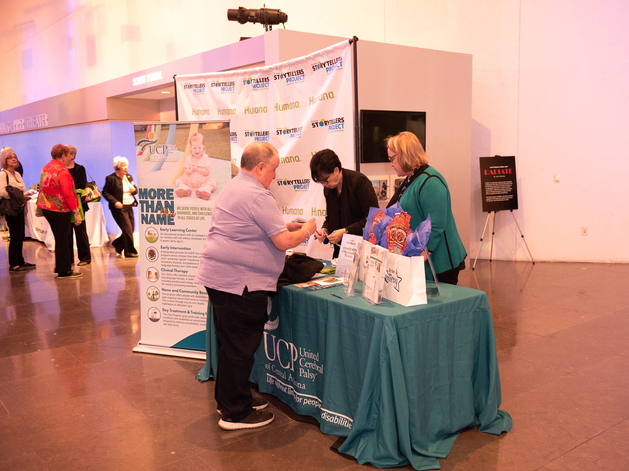 """An attendee visits the United Cerebral Palsy booth during """"Arizona Storytellers: Romance or Not"""" at the Scottsdale Center for Performing Arts on Wednesday, Feb. 13, 2019."""