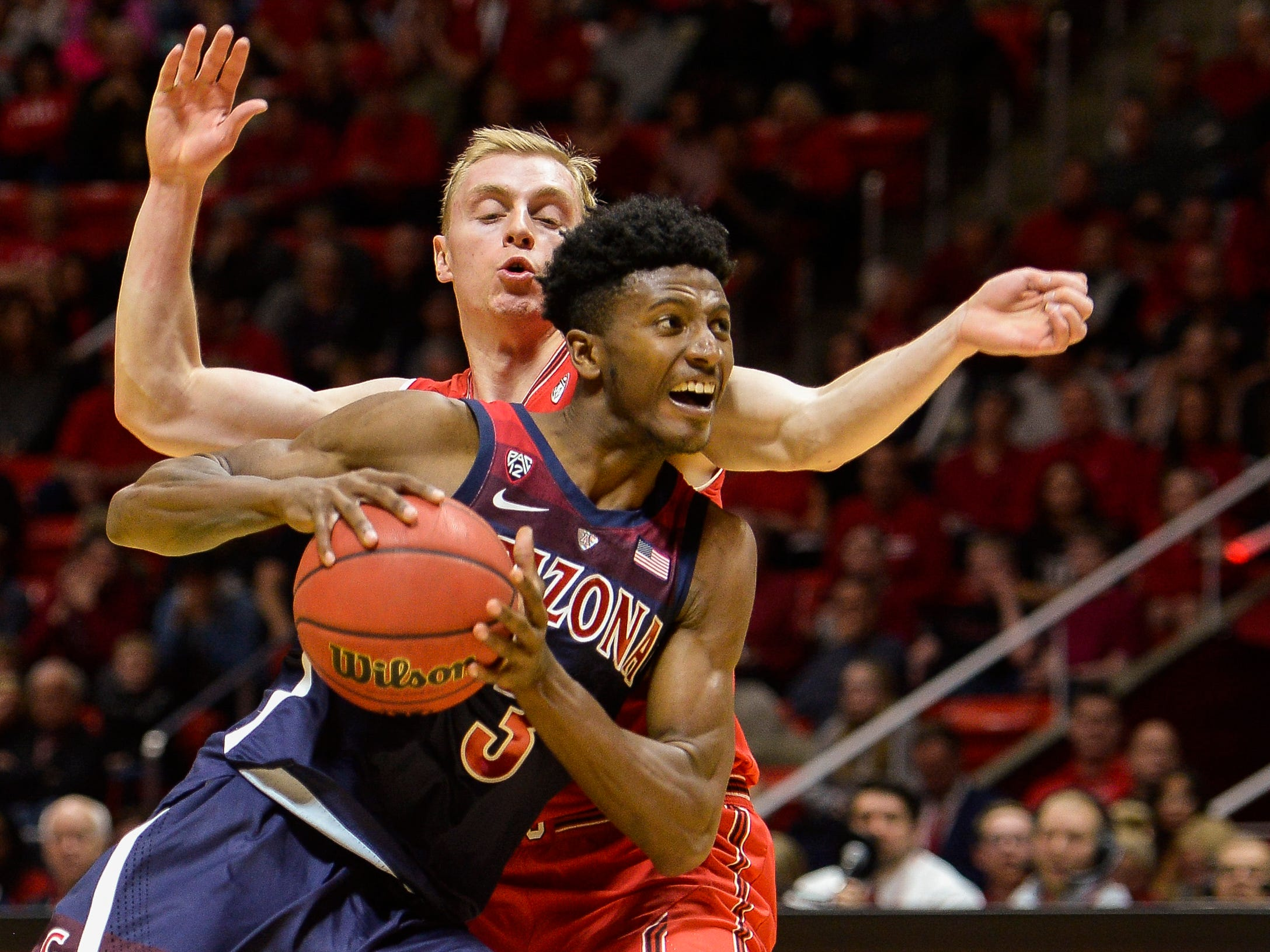 Arizona guard Dylan Smith, front, attempts to drive past Utah guard Parker Van Dyke, rear, during the first half of an NCAA college basketball game Thursday, Feb. 14, 2019, in Salt Lake City.