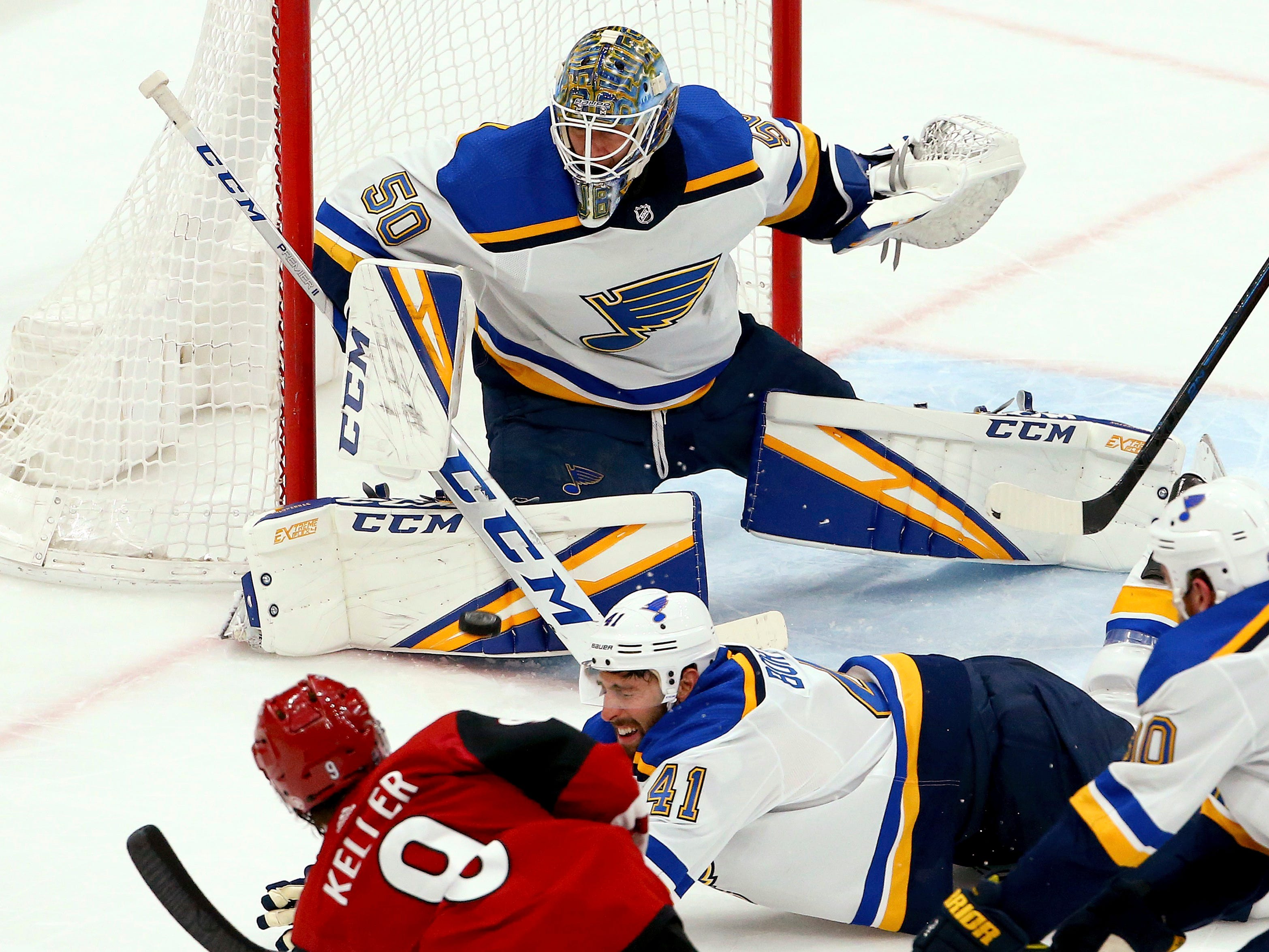 St. Louis Blues goaltender Jordan Binnington (50) makes a save on a shot by Arizona Coyotes center Clayton Keller (9) as Blues defenseman Robert Bortuzzo (41) and center Ryan O'Reilly (90) try to block the shot during the second period of an NHL hockey game Thursday, Feb. 14, 2019, in Glendale, Ariz.