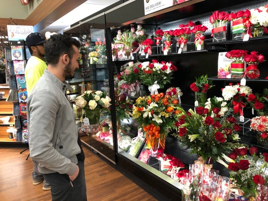 Luis Campas scans a refrigerated flower case, trying to decide between red and white roses.