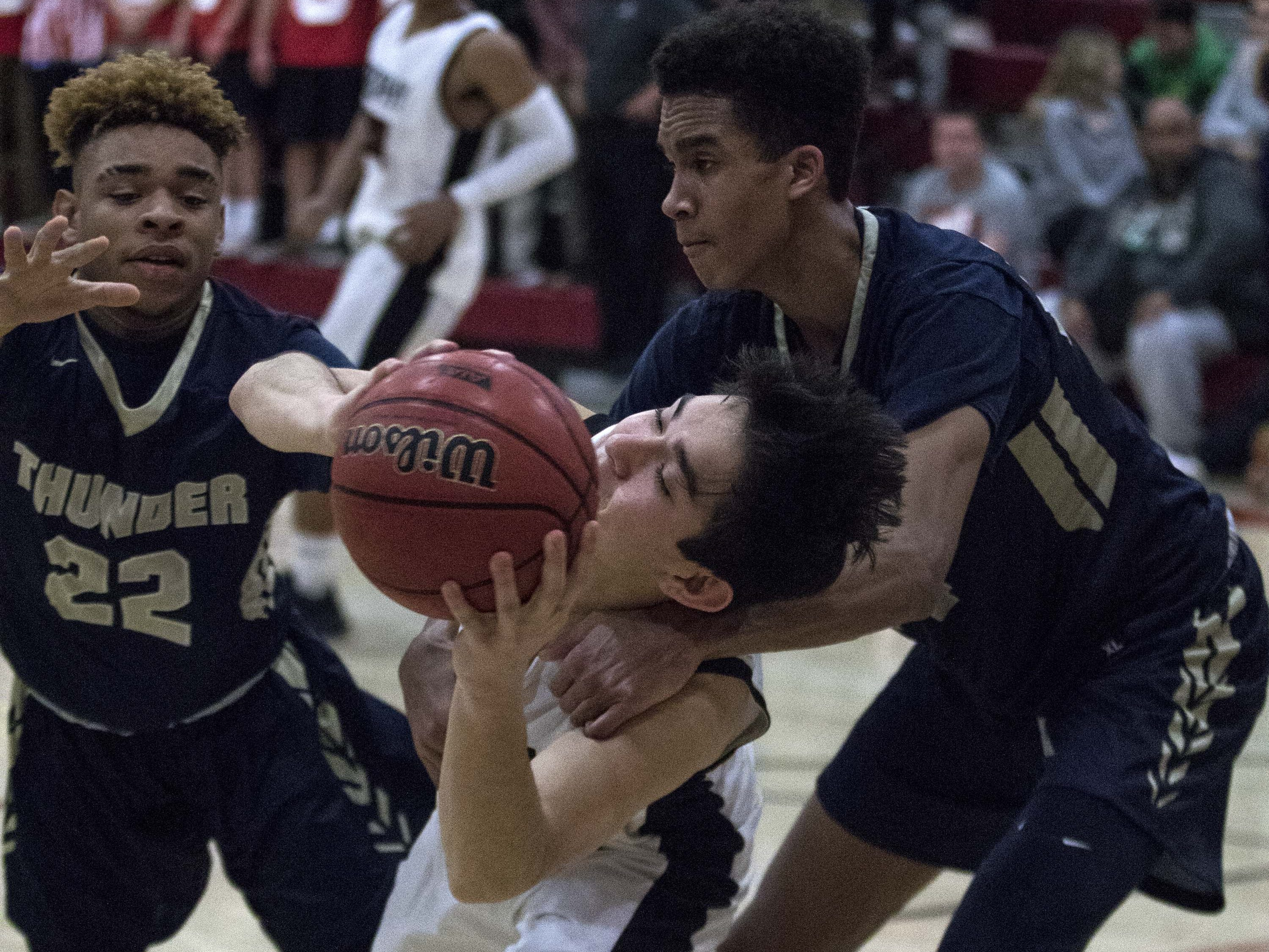 Brophy's Ethan Smith (0) is fouled by Desert Vista's Osasere Ighodaro (24) as Demaryea Gadson (22) goes for the ball during the second half of their game in Phoenix, Thursday, Feb .14,  2019.