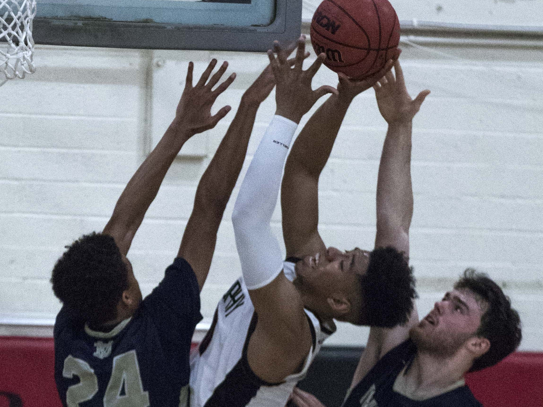 Brophy's Marques White(20) puts up a shot against Desert Vista's Osasere Ighodaro (24) and Mason Harbertson(12) during the second half of their game in Phoenix, Thursday, Feb .14,  2019.