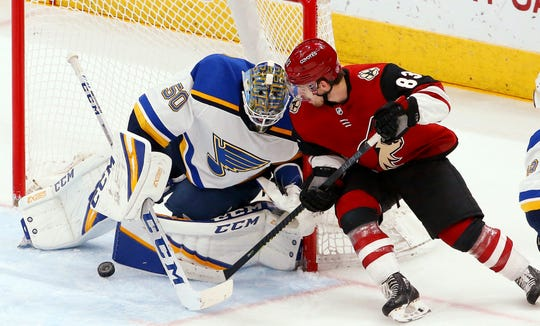 St. Louis Blues goaltender Jordan Binnington (50) makes a save on a shot by Arizona Coyotes right wing Conor Garland (83) during the first period of an NHL hockey game Thursday, Feb. 14, 2019, in Glendale, Ariz.