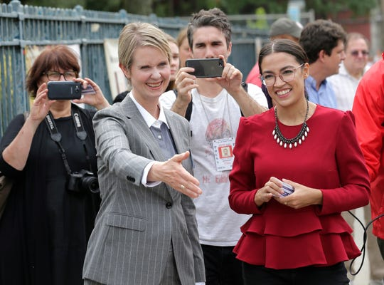 Alexandria Ocasio-Cortez wore the distinctive necklace made by Daphne Atkeson, a gift from her boyfriend's mother, while campaigning in New York in September 2018 with then-gubernatorial candidate Cynthia Nixon.