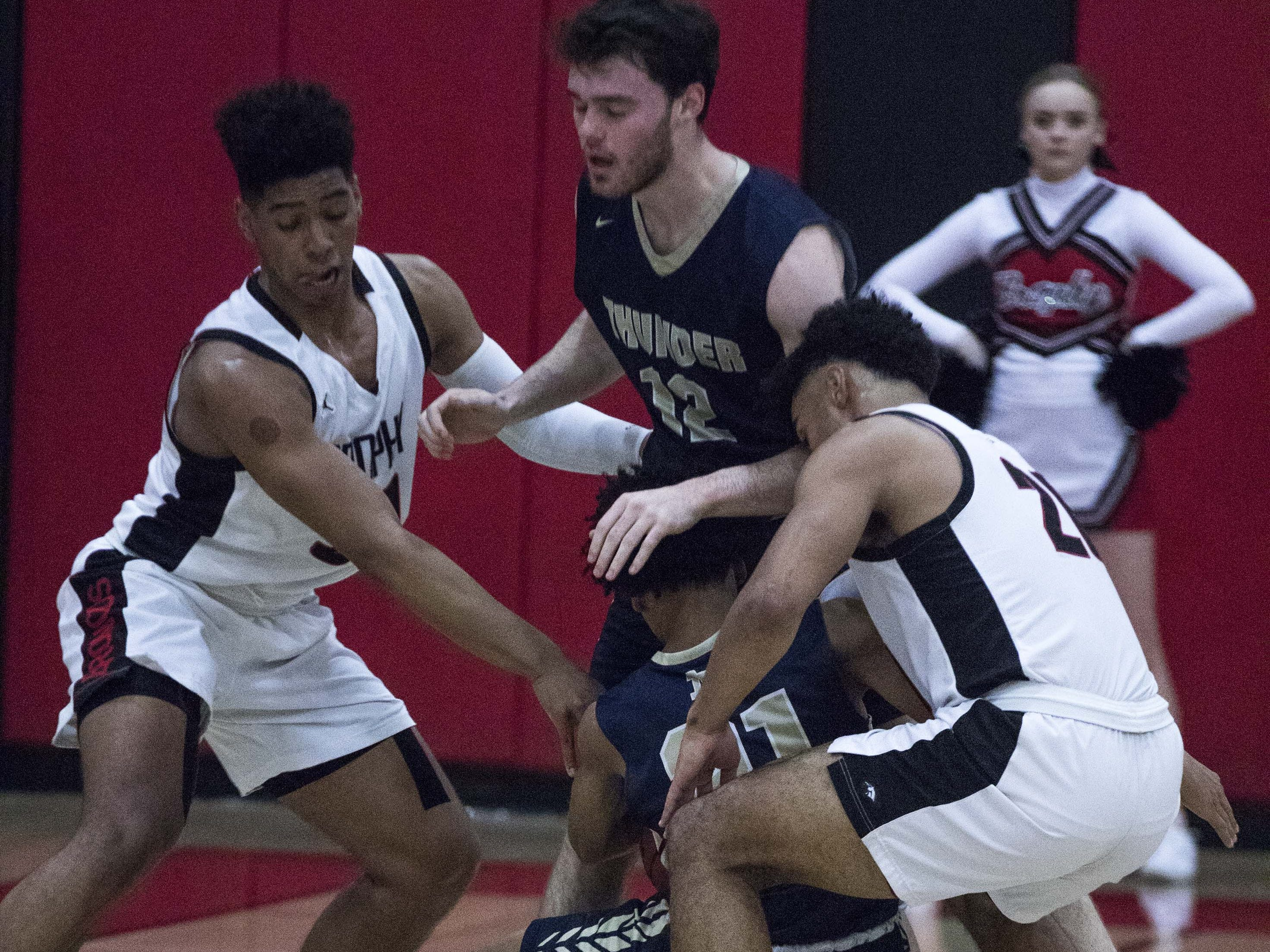 Brophy's Joe Feeney and Marques White (2) play tough defense on Desert Vista's Malik Mack (21) as he falls to the ground during the first half of their game with Desert Vista in Phoenix, Thursday, Feb .14,  2019.