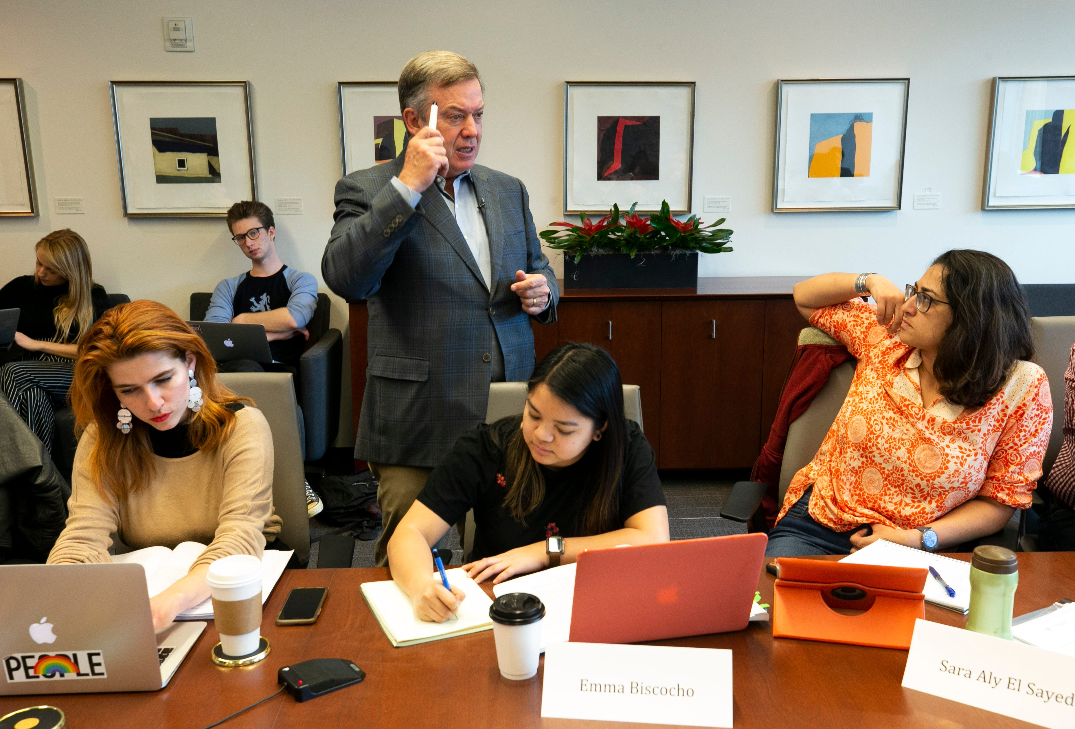 ASU President Michael Crow smiles while teaching the multi-discplinary Science, Technology and Public Affairs class to (from left at front) masters student Sarah Lords, masters student Emma Biscocho and doctoral candidate Sara Aly El Sayed, along with other ASU doctoral, masters and undergraduate students at the Fulton Center at ASU in Tempe on Jan. 30, 2019.