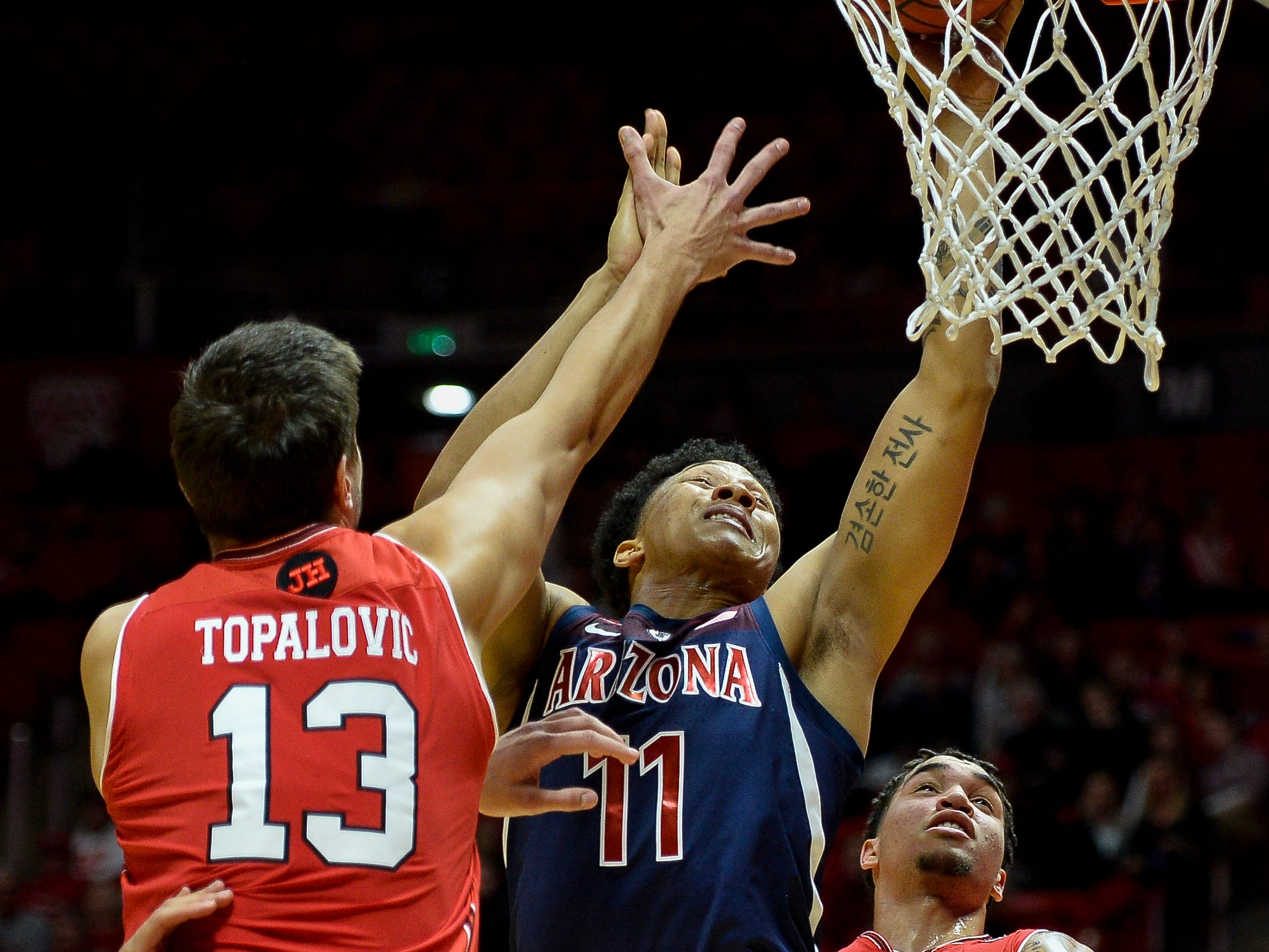 Arizona forward Ira Lee (11) attempts a shot between Utah forwards Novak Topalovic, left, and Timmy Allen, right, during the first half of an NCAA college basketball game Thursday, Feb. 14, 2019, in Salt Lake City.