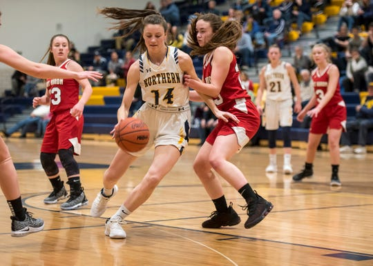 Port Huron Northern's Sarah Wight (14) dribbles the ball around Port Huron High School forward Morgan James during an MAC tournament basketball game Thursday, Feb. 14, 2019 at Port Huron Northern High School.