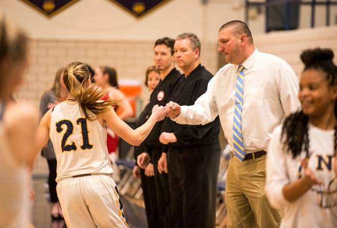 Port Huron Northern head coach Kevin Landschoot, right, fist-bumps sophomore Ally Shagena before an MAC tournament basketball game Thursday, Feb. 14, 2019 at Port Huron Northern High School.