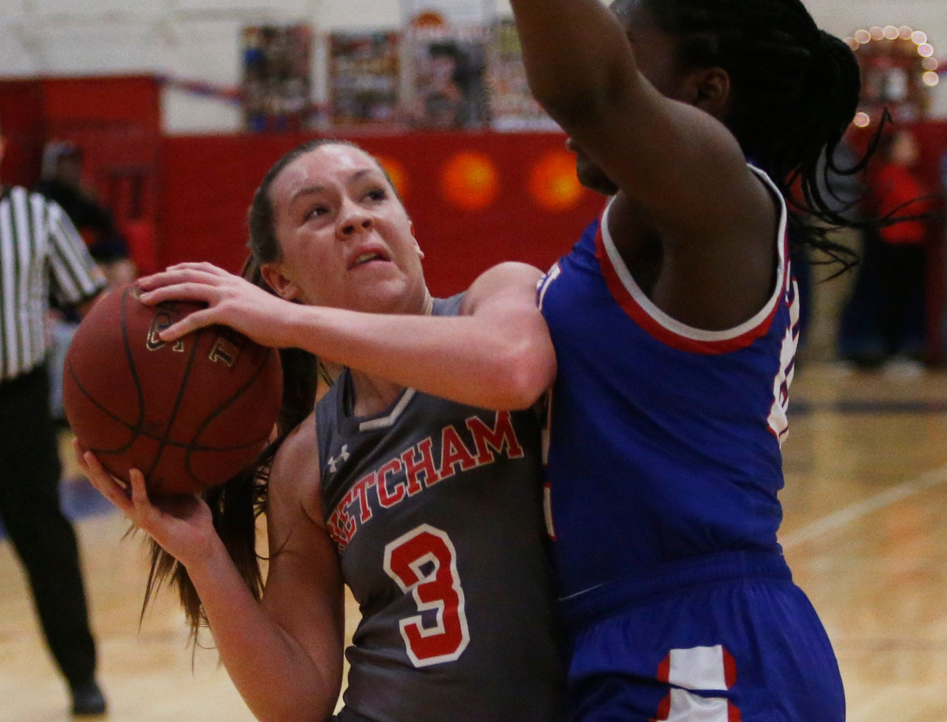 Ketcham's Katie Wall goes up for a shot while closely guarded by Carmel's Stephanie Ogbebor during a Feb. 14 game.