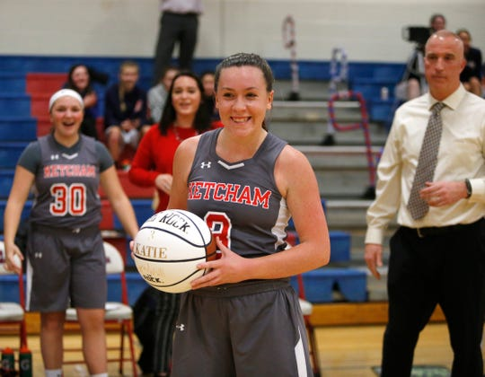 Ketcham senior Katie Wall poses with a commemorative ball during a fourth-quarter ceremony following her 2,000th career point on Feb. 14.