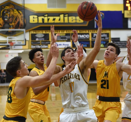 Galena's Chase Nelson is surrounded by Manogue players as he reaches for a rebound during Tuesday's game at Galena.