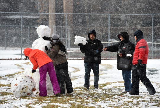 The Liu family from San Francisco builds a snowman as the snow falls at Wingfield Park in downtown Reno on Friday Feb. 15, 2019. More snow is expected through Sunday in the Reno area.