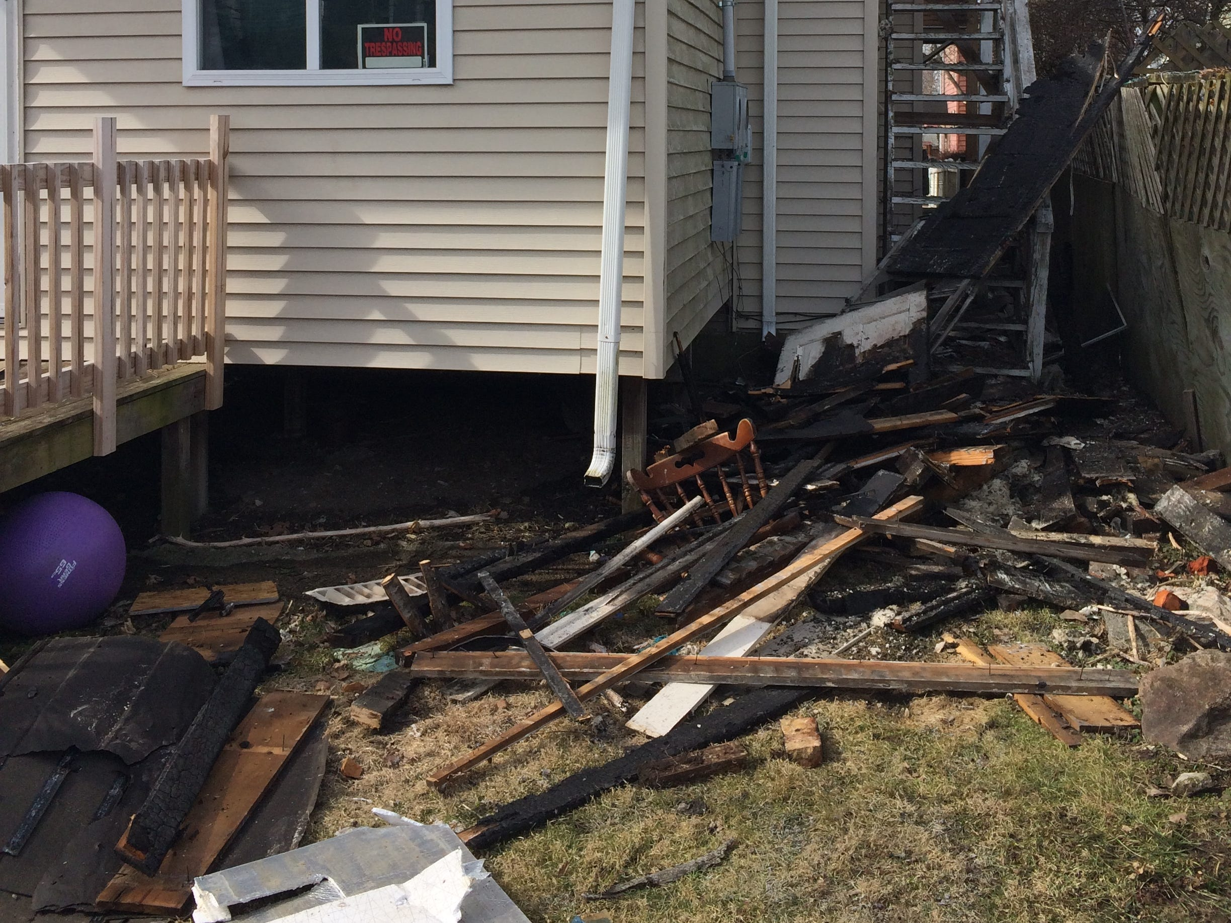 Charred materials litter the backyard and damage to an upstairs apartment is visible after a Friday morning fire on South 12th Street.