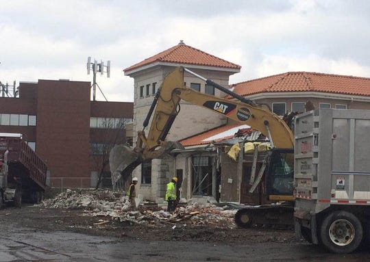 Crews began tearing down the old Mario's restaurant Friday.