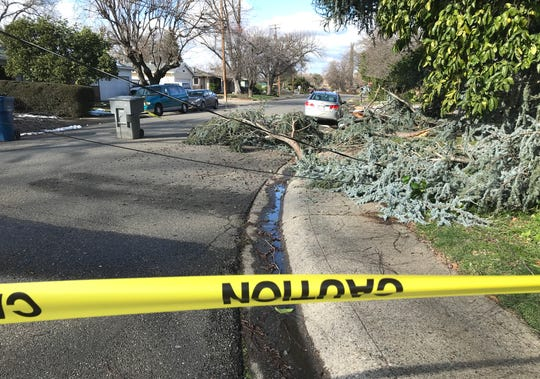 Caution tape blocks drivers near the intersection of Athens and London avenues in Redding where tree branches and power lines had fallen across the street during this week's snowstorm.