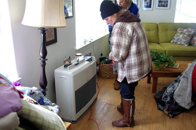 Sharon Denning, foreground, and her daughter-in-law, McKenna Denning, try to get a kerosene heater working. The Dennings have been without power at their Shingletown home since Tuesday night, when they received about 3 feet of snow.