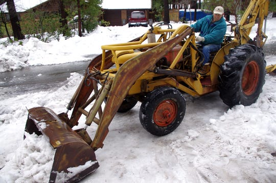 Andrew Belli, 85, plows snow in front of his home in Shingletown on Thursday.
