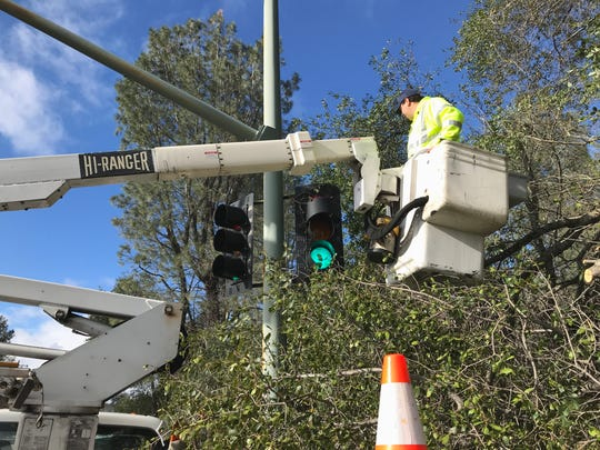 Shaun Vega Sanchez, an electrical technician with the city of Redding, works Friday afternoon to fix a tunnel visor on a stoplight that was damaged by a falling tree in this week's snowstorm on Bechelli Lane near South Bonnyview Road. Sanchez also used a chainsaw to make a pile of the branches.