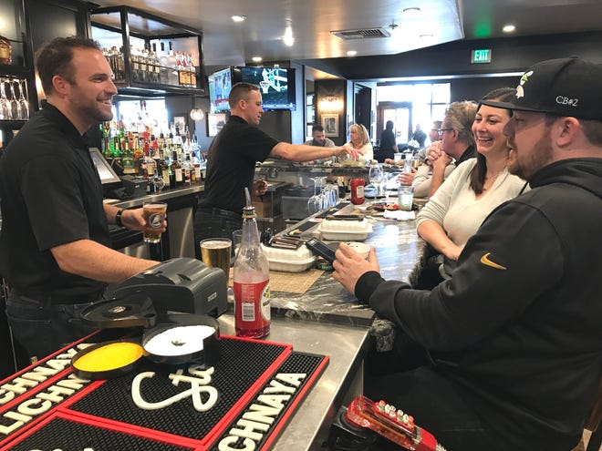 Chris Zettel, left, food and beverage manager at C.R. Gibbs American Grille, serves customer Hilari Schwartz, and Shawn Brubaker, right, who's a bartender at the Redding restaurant but was off Friday. C.R. Gibbs was able to open Thursday in time to serve Valentine's Day dinners.