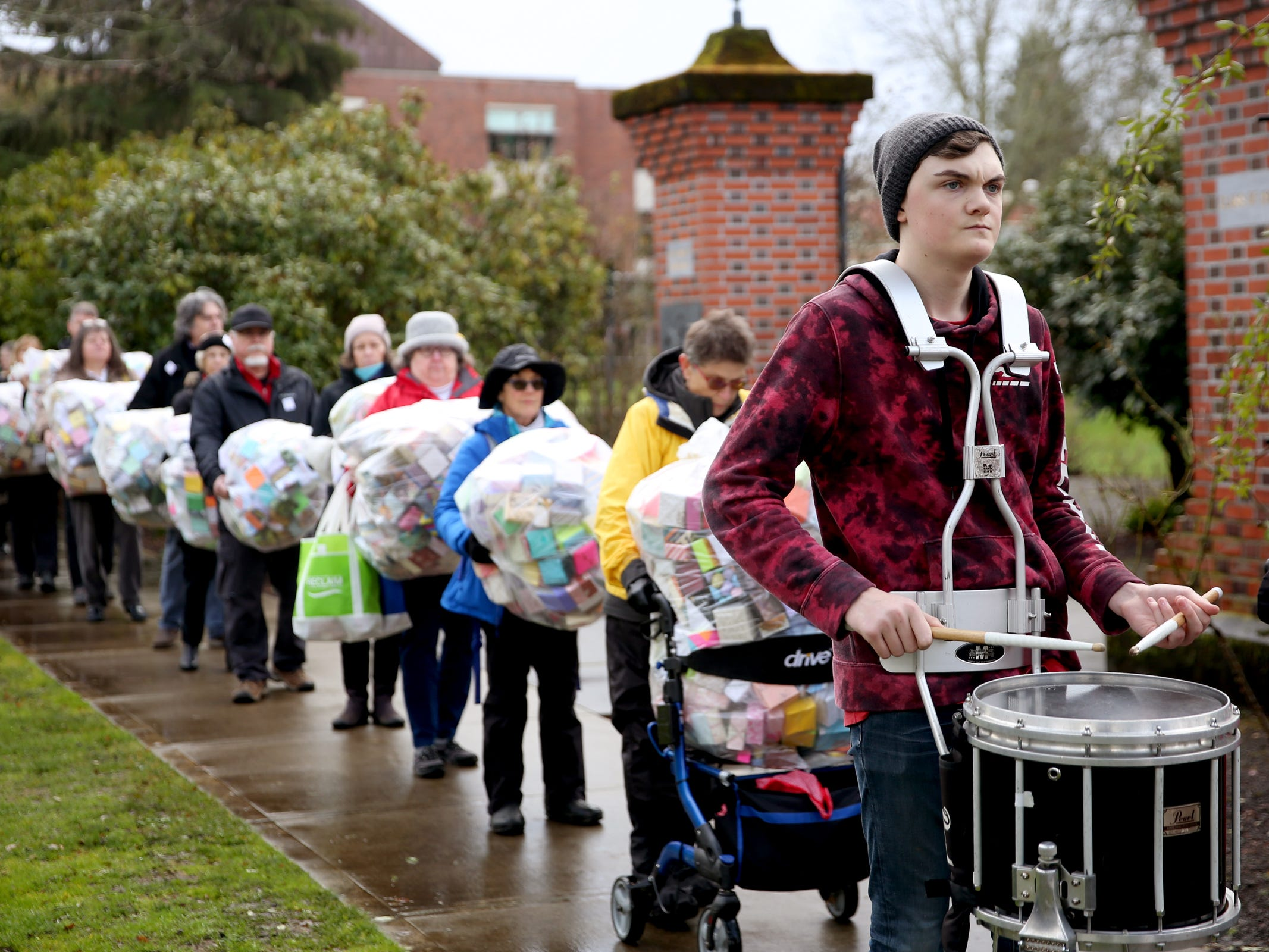 More than 100 people, led by drummer Tristan Kruger, deliver and display more than 37,000 handmade origami boxes, representing victims of gun violence, at the Oregon State Capitol in Salem on Friday, Feb. 15, 2019. The Soul Box Project, started by Portland artist Leslie Lee, aims to reveal the enormity of the gun fire epidemic.
