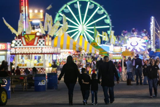 A family walks in the carnival during the San Angelo Stock Show & Rodeo Thursday, Feb. 14, 2019, at the fairgrounds.