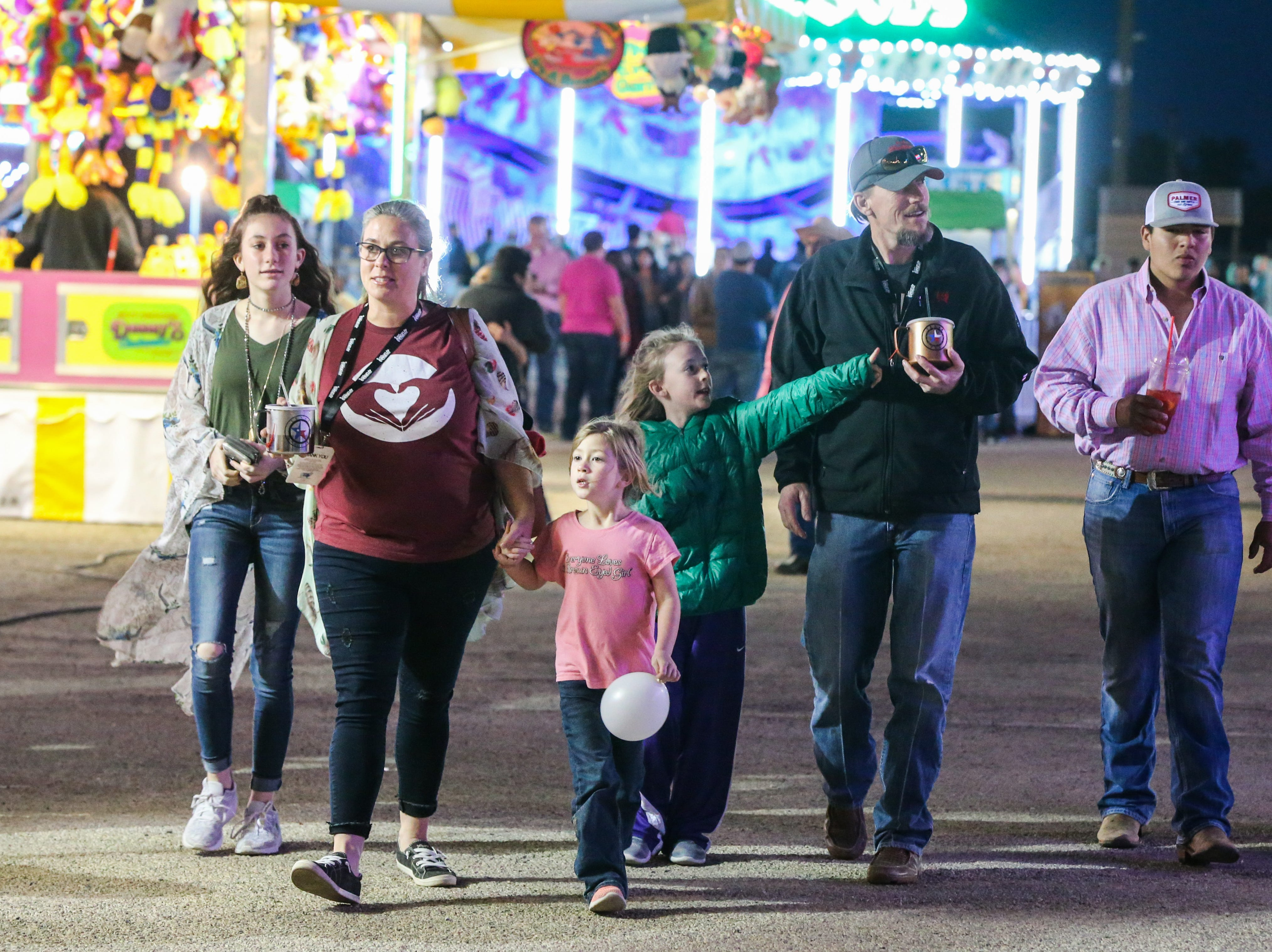 The Halliburton family walks around the carnival during the San Angelo Stock Show & Rodeo Thursday, Feb. 14, 2019, at the fairgrounds.
