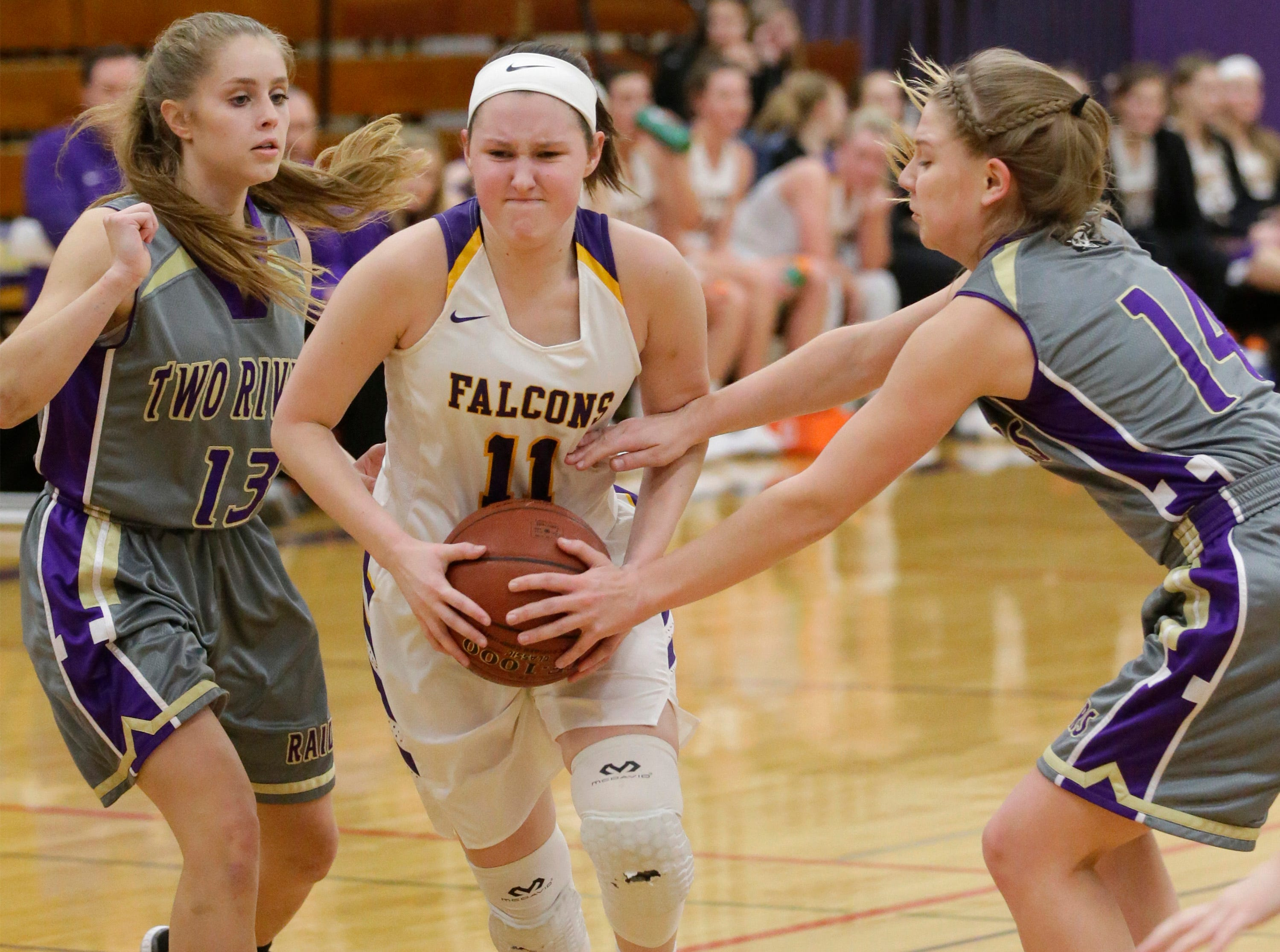 Sheboygan Falls' Claire Smallwood (11) grips the ball by Two Rivers players, Thursday, February 14, 2019, in Sheboygan Falls, Wis.