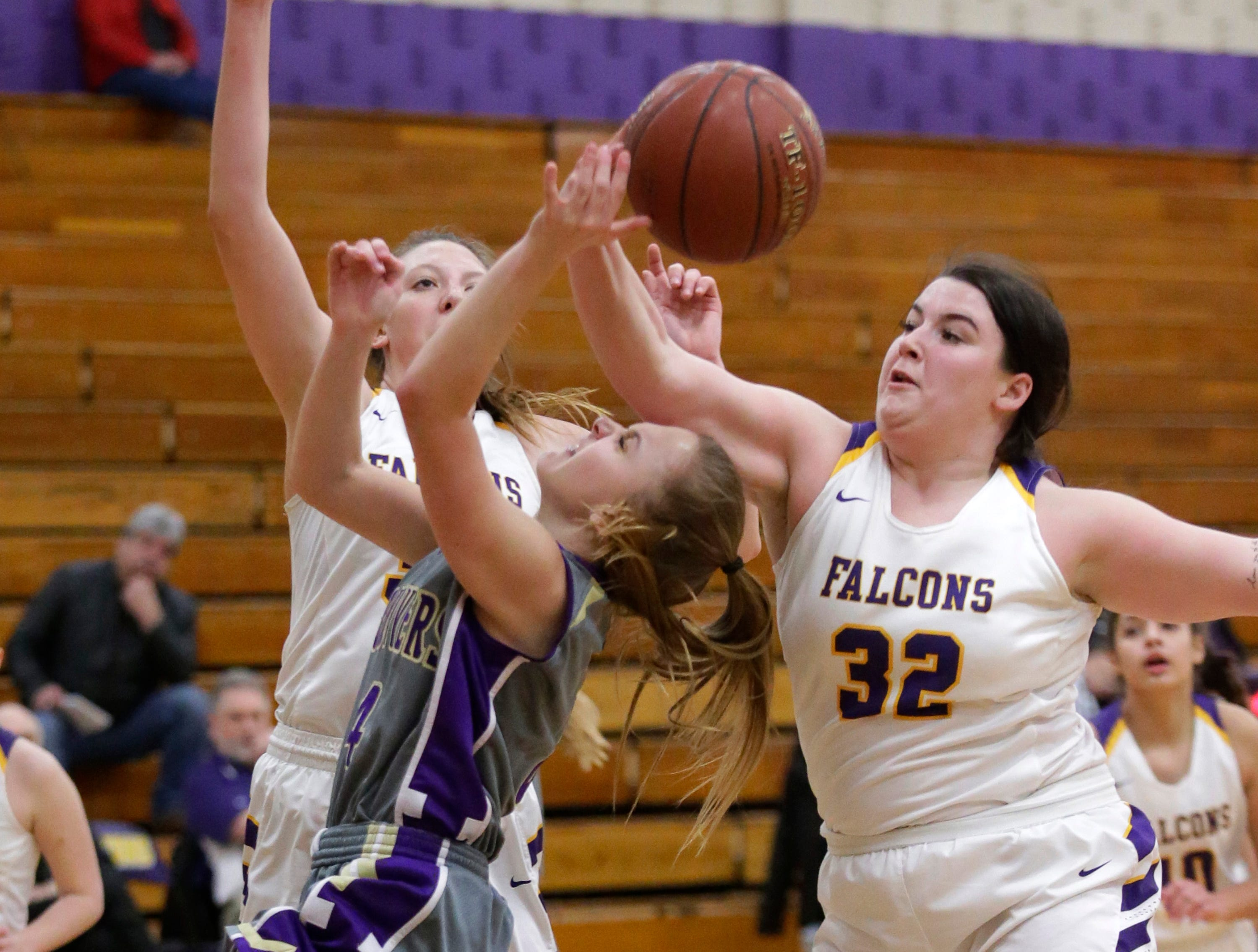 Two Rivers' Mackenzie Greenwood (4, in grey) grips the ball while Sheboygan Falls' Alayna Milne (32) tries to pull the ball from Greenwood's grasp., Thursday, February 14, 2019, in Sheboygan Falls, Wis.