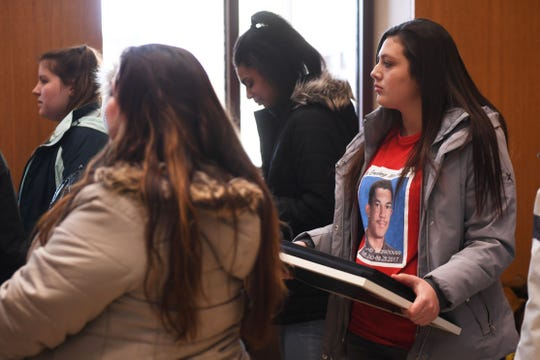 Kina Bearsheart, Riley Stonehouse's cousin, holds photos of him at the Lincoln County Courthouse Friday, Feb. 15, after Dylan Holler was sentenced in Canton. Holler was sentenced to 80 years in the penitentiary, with 40 suspended, for the shooting death of Susie Stonehouse's son 17-year-old Riley Stonehouse in August 2017.