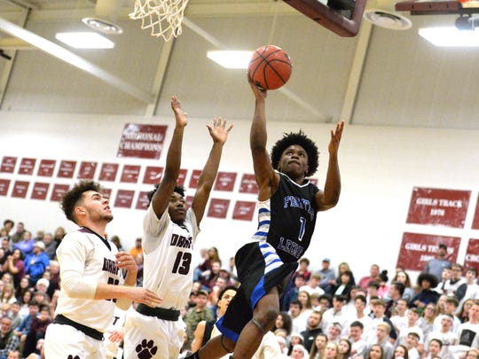 Lee High's Javon Battle takes the ball to the basket Thursday against Stuarts Draft's Tyler Goodwin and Jo'el Howard (13).