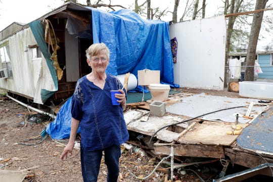 Joy Boutwell stands in front of the trailer she rents in Bristol, Fla., Friday Feb. 15, 2019. The back portion of the trailer was ripped off by Hurricane Michael in Oct. 2018. Bautwell continues to reside in the trailer despite the damage.