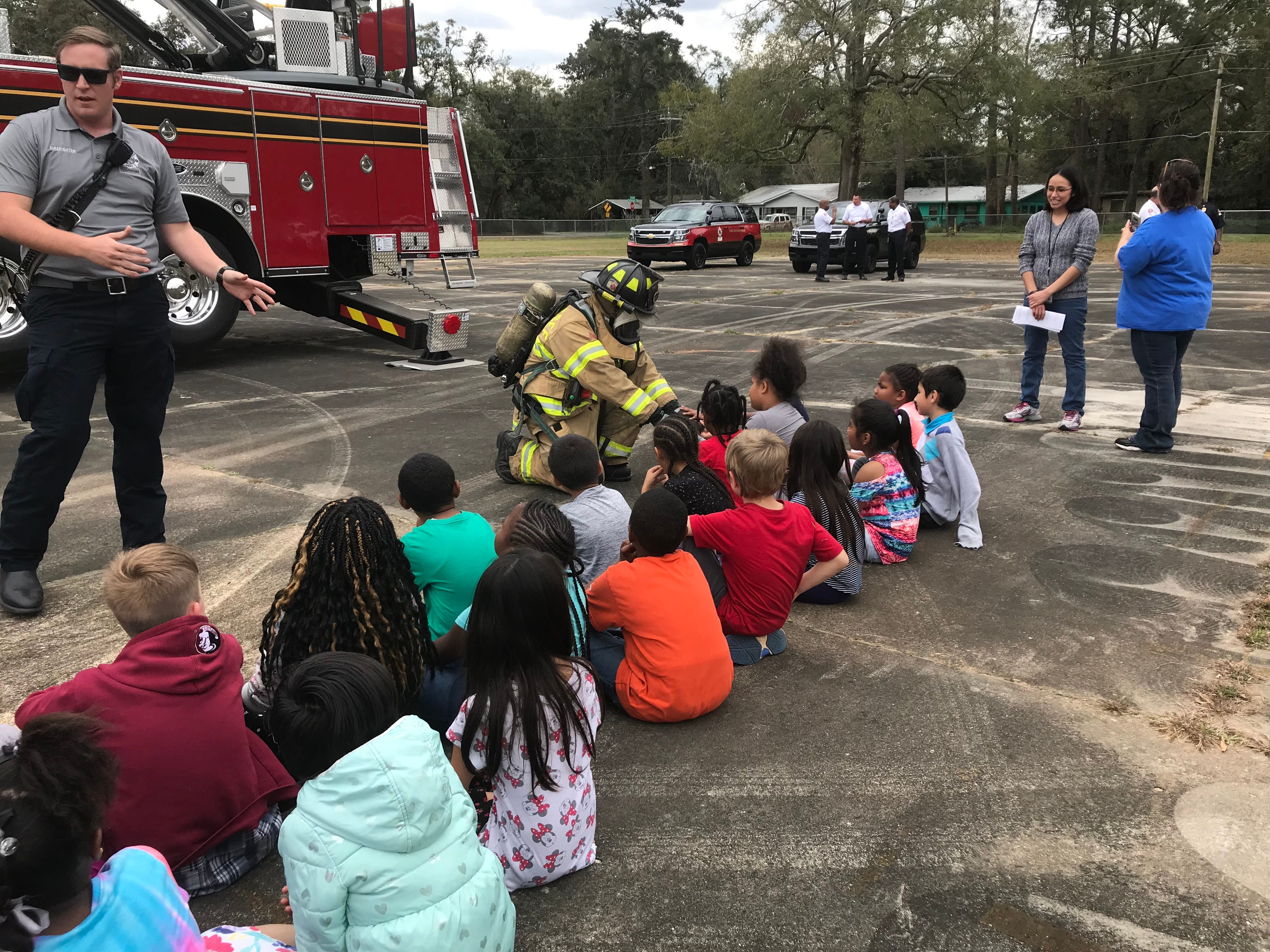 Firefighter Tom Burns, left, tells Sabal Palm Elementary second graders not to be afraid of first responders who may come to their house in an emergency while Engineer Jeff Brady lets students feel his gloves while visiting the school Friday.
